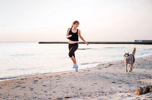husky siberiano haciendo ejercicio con mujer joven